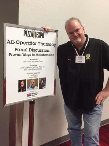 Rick Drury Next to Signage at Pizza Expo